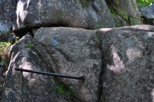 An iron rung hammered into the rock face of a steep slope.